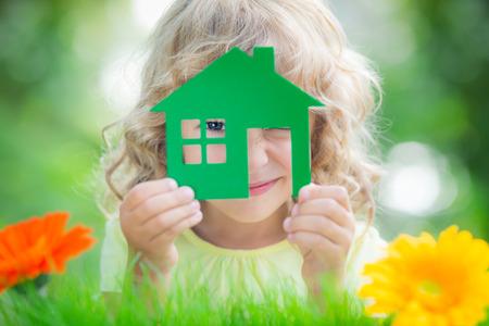 Boldog gyermek gazdaság házban kezében elleni tavaszi zöld háttér. Ingatlan üzleti koncepció
