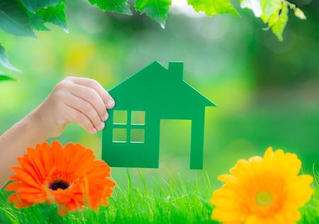 봄 녹색 배경에 손에 녹색 종이 집. 부동산 비즈니스 개념