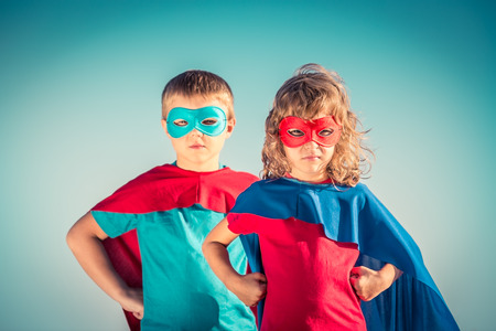 bambini felici: Bambini Superhero contro sfondo del cielo estivo. Bambini che hanno divertimento all'aperto. Ragazzo e ragazza che giocano. Il successo e vincitore concetto