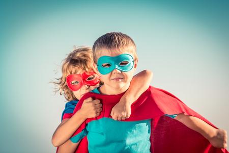 niñez: Niños Superhero contra fondo del cielo de verano. Niños que se divierten al aire libre. Niño y niña jugando. El éxito y el concepto del ganador