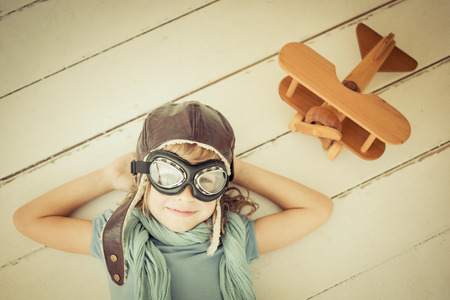 Happy child playing with toy airplane. Unusual high angle view portrait of kid on wood background. Retro toned Stock Photo