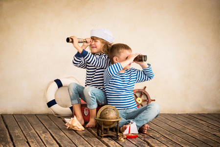 Děti si hrají s vintage námořních věcí. Děti baví doma. Cestování a dobrodružství koncept. Retro tónovaný obraz