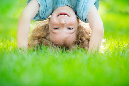 Happy child standing upside down on green grass. Laughing kid having fun in spring park. Healthy lifestyle concept