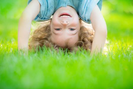 bambini: Bambino felice in piedi a testa in gi� sull'erba verde. Ridere bambino divertirsi nel parco di primavera. Concetto di stile di vita sano