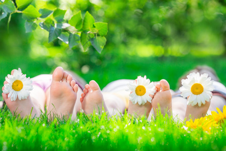 Happy family lying on green grass. Children having fun outdoors in spring park