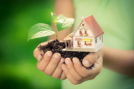 Dítě drží dům a strom v ruce proti jarní zelené pozadí. Realitní koncepce Reklamní fotografie
