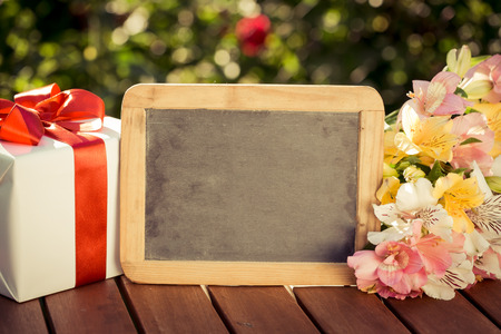 Blackboard blank, gift box and flowers against spring background. Womens day concept.