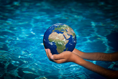 Child holding 3D planet in hands against blue water background. Earth day holiday concept. Elements of this image furnished by NASA