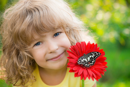 Beautiful child with butterfly in spring park. Happy kid playing outdoors photo