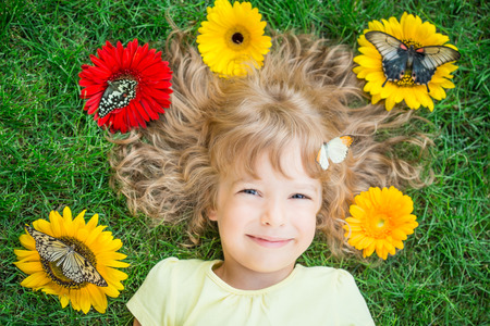 Beautiful child with butterfly in spring park. Happy kid lying on green grass outdoors photo