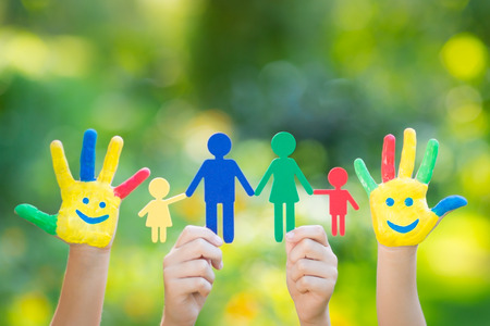 Paper family in hands against spring green background. Ecology concept Stock Photo
