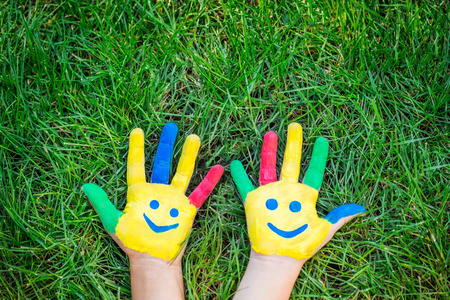 green smiley face: Smiley hands on green grass. Children having fun in spring outdoors. Ecology concept
