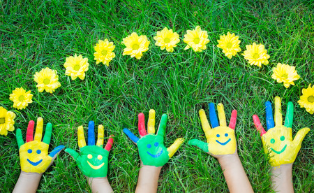 smiley: Group of happy people on green grass. Family having fun in spring. Smiley on hands. Ecology concept. Top view portrait