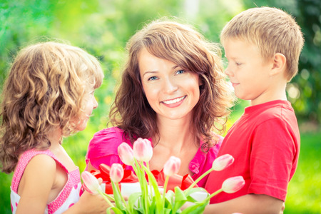 three presents: Happy family with bouquet of flowers and gifts outdoors. Young beautiful mother with son and daughter lying on green grass. Spring holiday concept. Womens day concept