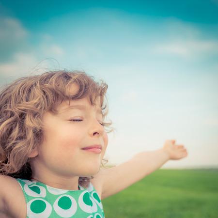 春の野で幸せな子。少女屋外でリラックスします。自由の概念