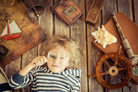 Happy kid playing with nautical things. Child having fun at home. Travel and adventure concept. Unusual high angle view portrait Stock Photo