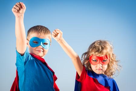 Superhero children against summer sky background. Kids having fun outdoors. Boy and girl playing. Success and winner concept Standard-Bild