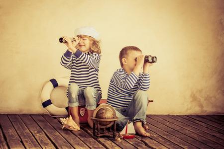 maletas de viaje: Niños que juegan con las cosas náuticas de la vendimia. Niños que se divierten en el país. Viajes y la aventura concepto. Imagen en tonos retro