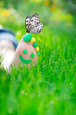 joy health: Child lying on green grass. Kid having fun outdoors in spring park