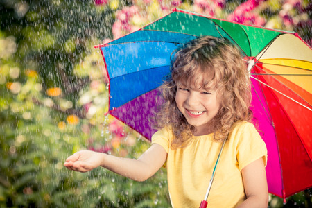 lluvia paraguas: Niño feliz en la lluvia. Cabrito divertido jugando al aire libre en el parque de la primavera