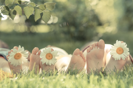 woman foot: Happy family lying on green grass. Children having fun outdoors in spring park. Retro toned Stock Photo