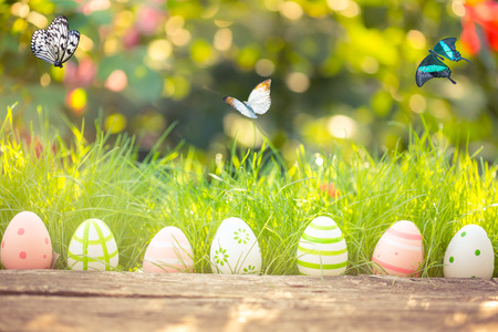 Easter eggs in grass against blurred green background. Spring holidays concept 스톡 콘텐츠