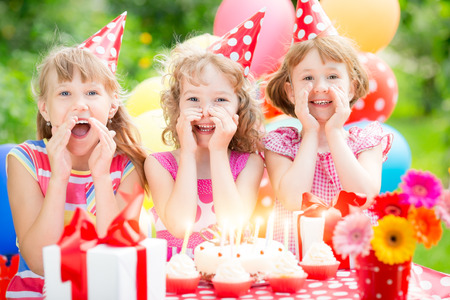 fiesta familiar: Grupo de niños felices que celebran cumpleaños. Niños que se divierten en el jardín de primavera