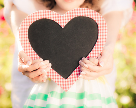 Happy woman and child holding heart shape blackboard blank against spring background. Family holiday concept. Mothers day photo