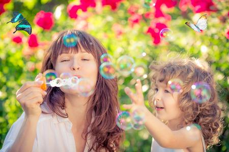mother and children: Familia feliz divertirse al aire libre en el parque de primavera contra el fondo verde natural Foto de archivo