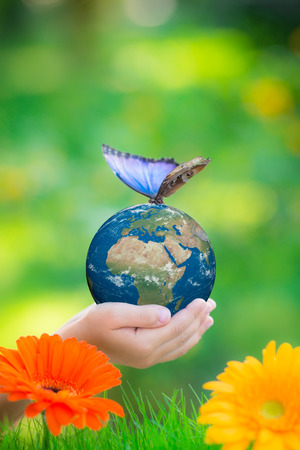 Child holding Earth planet with blue butterfly in hands against green spring background. Elements of this image furnished by NASA