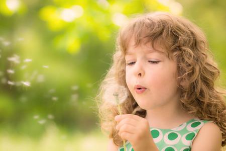 봄의 공원에서 민들레 꽃과 함께 아름 다운 아이입니다. 행복한 아이 재미 야외