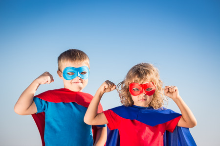 Superhero children against summer sky background. Kids having fun outdoors. Boy and girl playing. Success and winner concept Foto de archivo