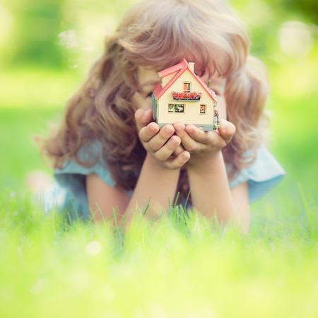 Kind hält Haus in den Händen gegen grünen Hintergrund Frühjahr. Immobilien-Konzept