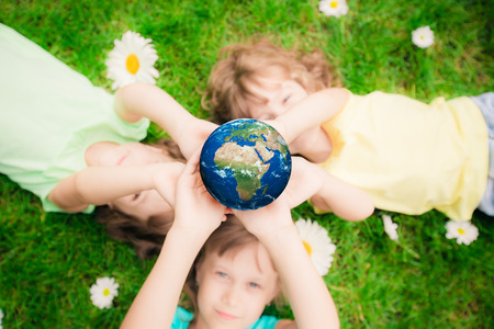 Children holding 3D planet in hands against green spring background. Earth day holiday concept. Elements of this image furnished by NASA photo