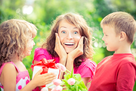 Happy family with bouquet of flowers and gifts outdoors. Young beautiful mother with son and daughter lying on green grass. Spring holiday concept. Mothers day. Surprise and joy Stock Photo