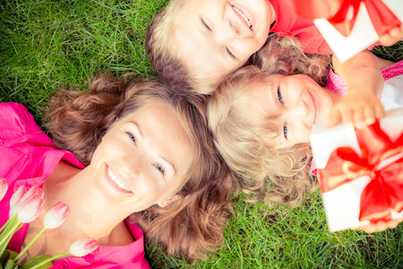 Happy family with bouquet of flowers and gifts outdoors. Young beautiful mother with son and daughter lying on green grass. Spring holiday concept. Mothers day. Unusual top view portrait