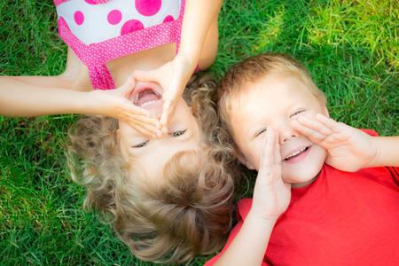 communication: Enfants drôles criant à l'extérieur. Enfants heureux couché sur l'herbe verte. Concept de communication