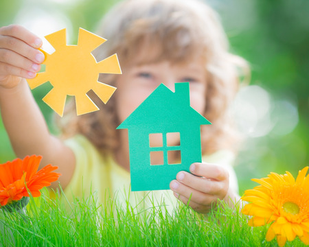 Happy child holding house and sun in hands against spring green background. Real estate business concept Stock Photo
