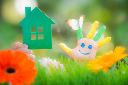 Green paper house in hands against spring green background. Real estate business concept