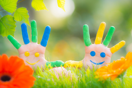 Happy smiley on hands against green spring background