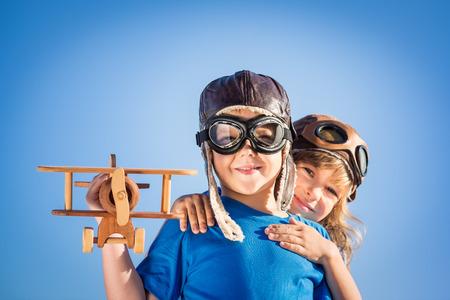 Gelukkig kinderen spelen met vintage houten vliegtuig. Portret van kinderen tegen de zomer hemel achtergrond Stockfoto