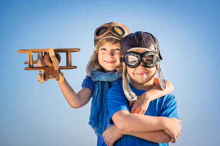 Happy kids playing with vintage wooden airplane. Portrait of children against summer sky background