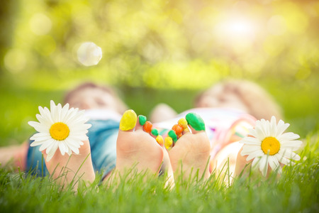 Couple lying on green grass. Children having fun outdoors in spring park Stock Photo