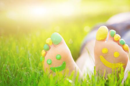 pies: Niño acostado en la hierba verde. Cabrito que se divierte al aire libre en el parque del resorte