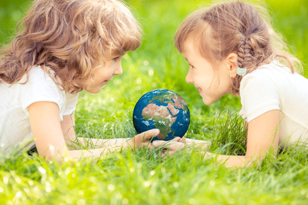 Child holding 3D planet in hands against green spring background. Earth day holiday concept.