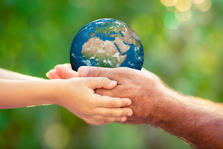 globe people: Child and senior holding 3D planet in hands against green spring background. Earth day holiday concept.