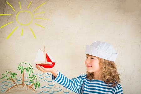 children: Счастливый ребенок играет с классическим Деревянная Игрушка корабля. Kid весело дома. Летний морской мечта и фантазия. Приключения и путешествия концепции. Ретро тонированные изображения