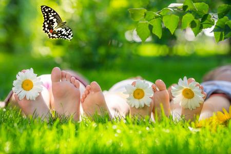 幸せな家族は、緑の芝生の上に横たわる。子供屋外スプリング パークで楽しんで