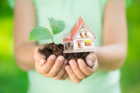 medio ambiente: Ni�o que sostiene la casa y �rbol en las manos contra el muelle de fondo verde. Concepto de bienes ra�ces Foto de archivo