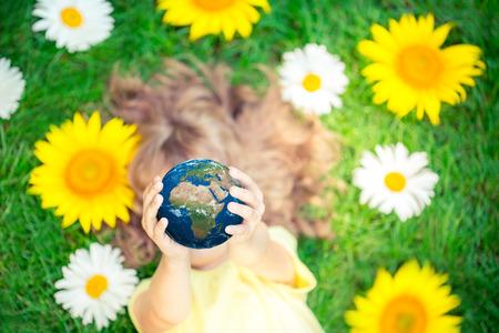 Niño que sostiene el planeta 3D en manos contra el fondo verde de la primavera. Concepto de vacaciones de Día de la Tierra. Los elementos de esta imagen proporcionada por la NASA Foto de archivo